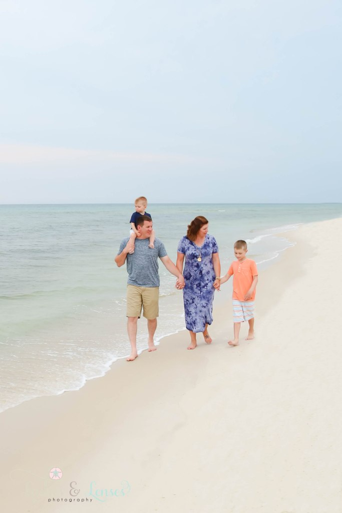 Family with two sons walking along the water at Johnsons Beach in Perdido Key Florida
