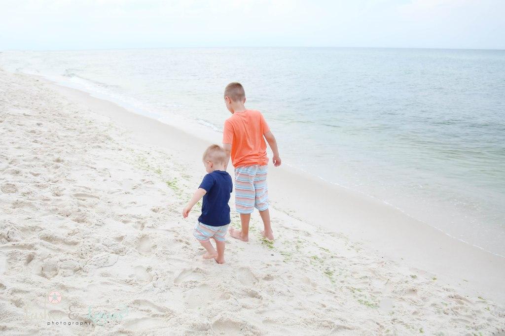 Brothers walking along the waters edge at Johnsons Beach in Perdido Key Florida