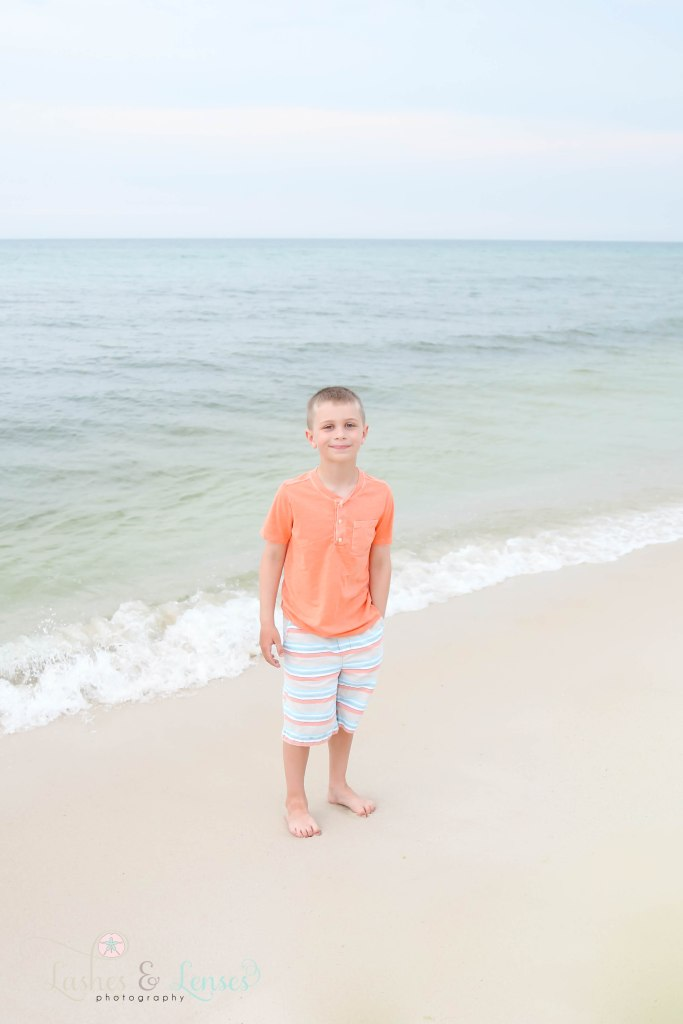 Elementary age boy standing next to the water at Johnsons Beach in Perdido Key Florida