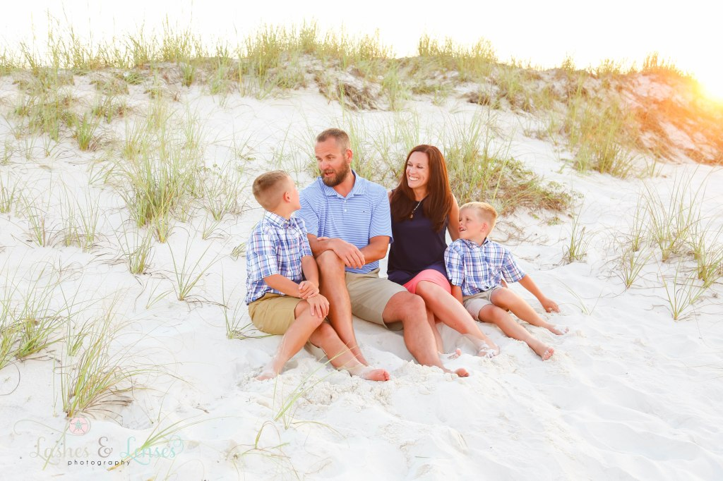 Mom and Dad sitting in the sand with their two elementary age sons at Johnsons Beach in Perdido Key Florida
