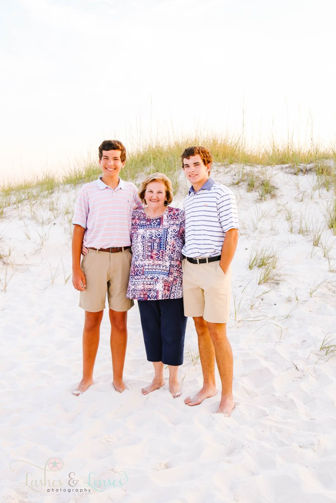 Grandma with her two teen grandsons standing next to the sand dunes at Johnsons Beach in Perdido Key Florida