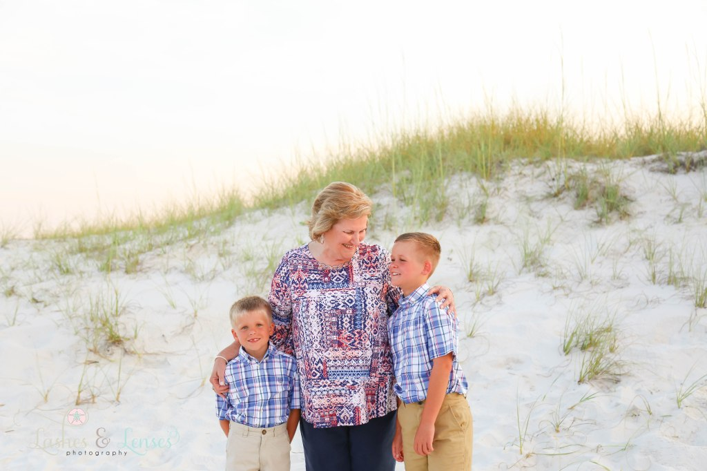 Grandma looking at her young grandsons with the sand dunes behind her at Johnsons Beach in Perdido Key Florida