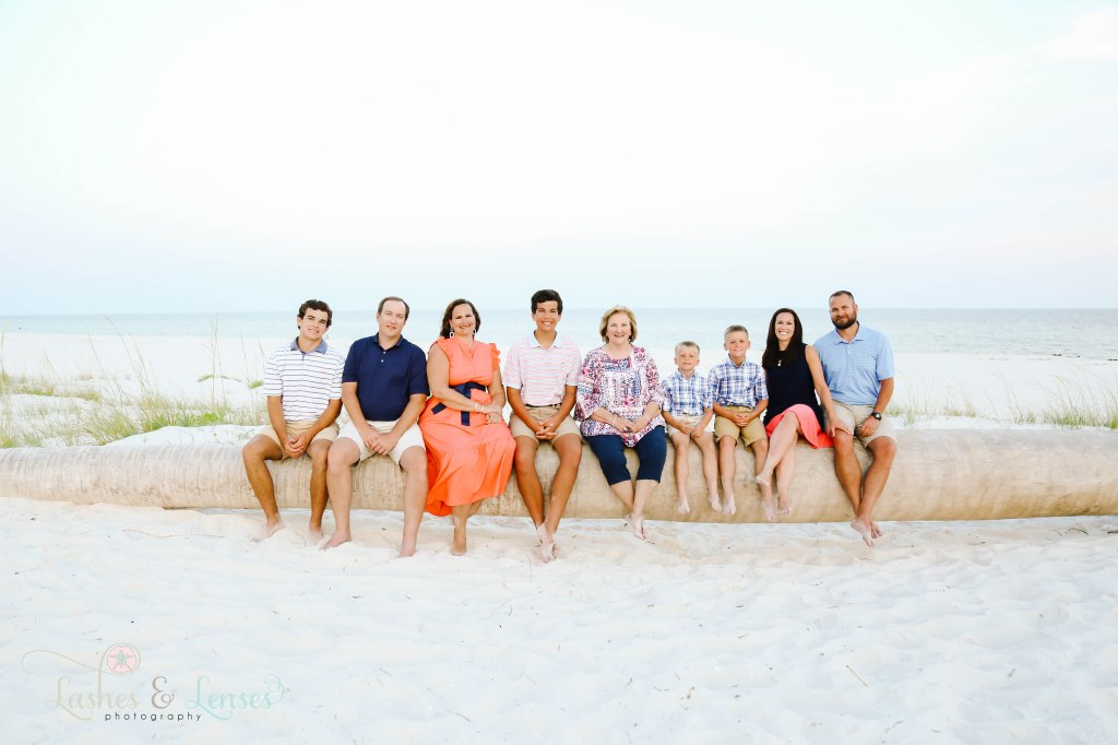 Extended family sitting on a washed up palm tree on the beach at Johnsons Beach in Perdido Key Florida