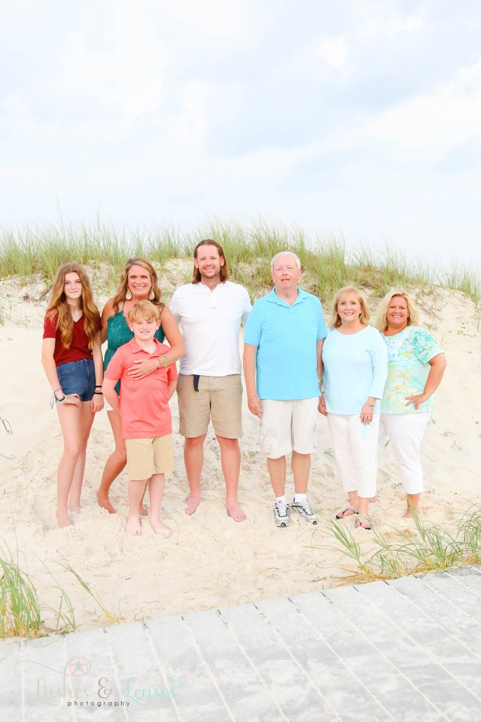 Extended family standing with the sand dunes behind them at Johnsons Beach in Perdido Key Florida