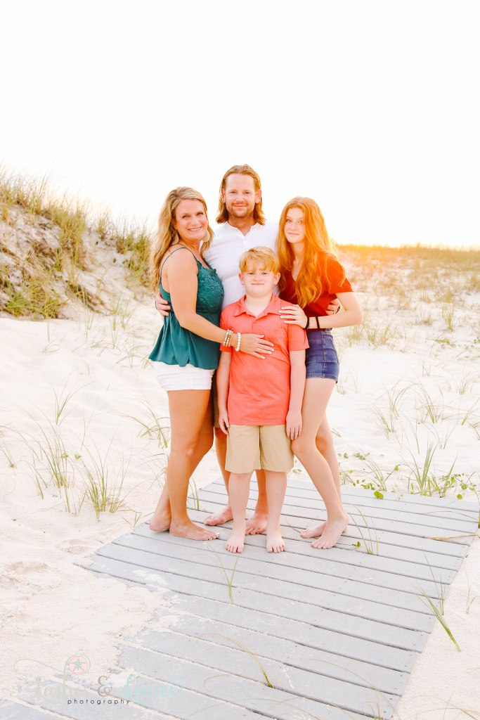 Mom and Dad with their teen daughter and pre-teen son standing on a washed up boardwalk at Johnsons Beach in Perdido Key Florida