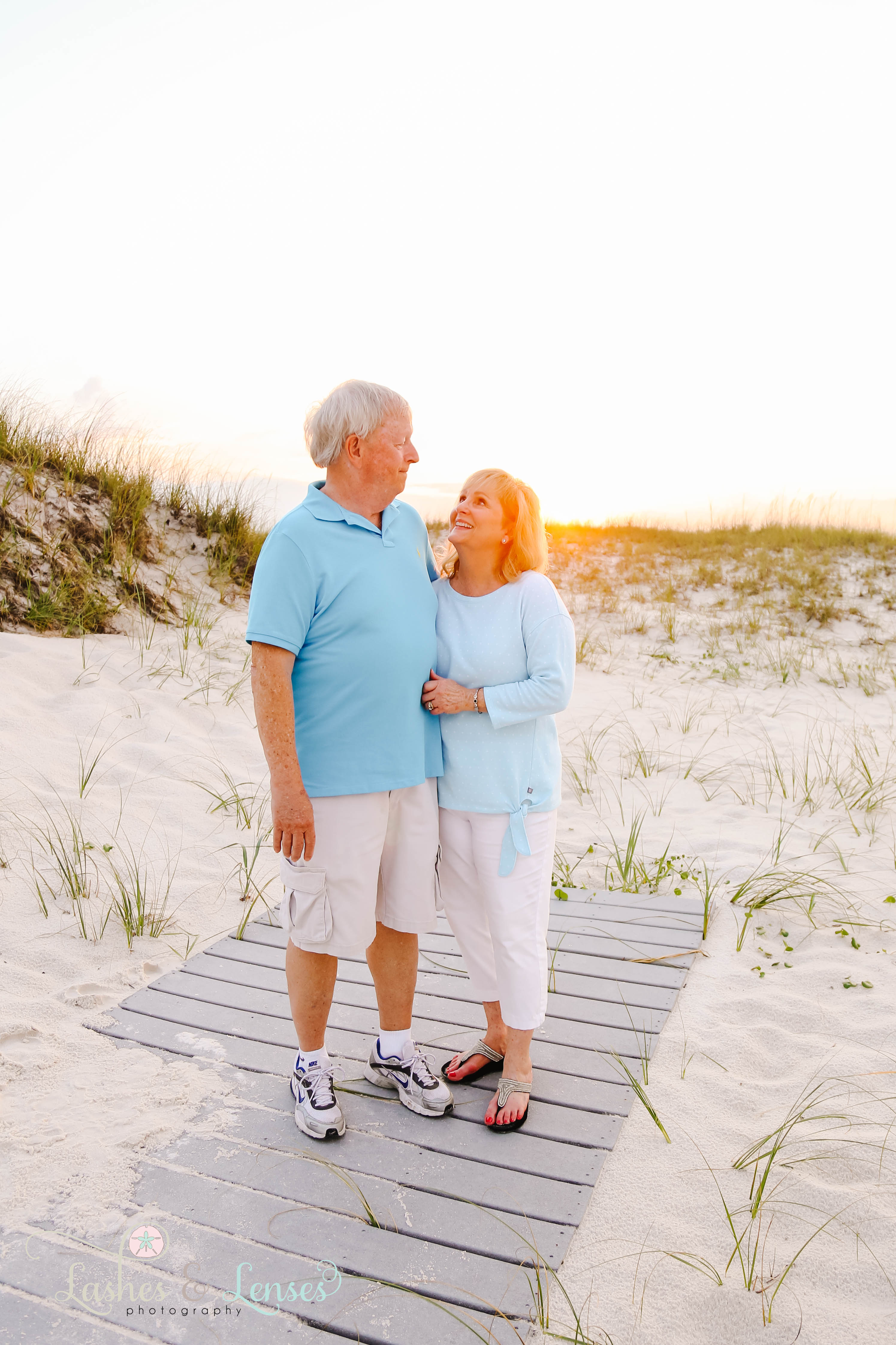 Couple looking at each other with the sunset behind them at Johnsons Beach in Perdido Key Florida