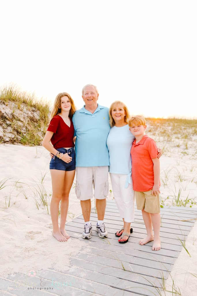 Grandma and Grandpa with their two grandchildren standing on a washed up boardwalk at Johnsons Beach in Perdido Key Florida