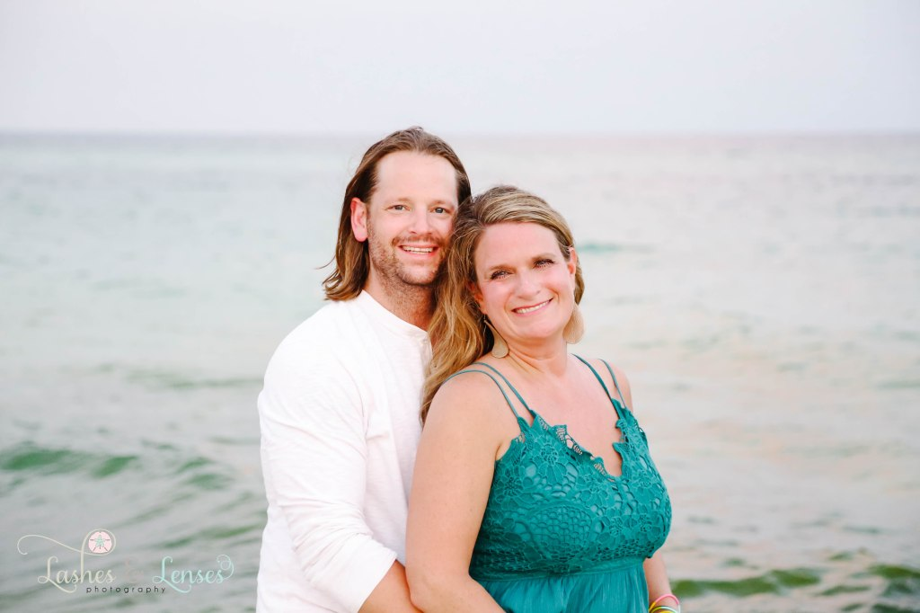 Couple looking right at the camera with the water right behind them at Johnsons Beach in Perdido Key Florida