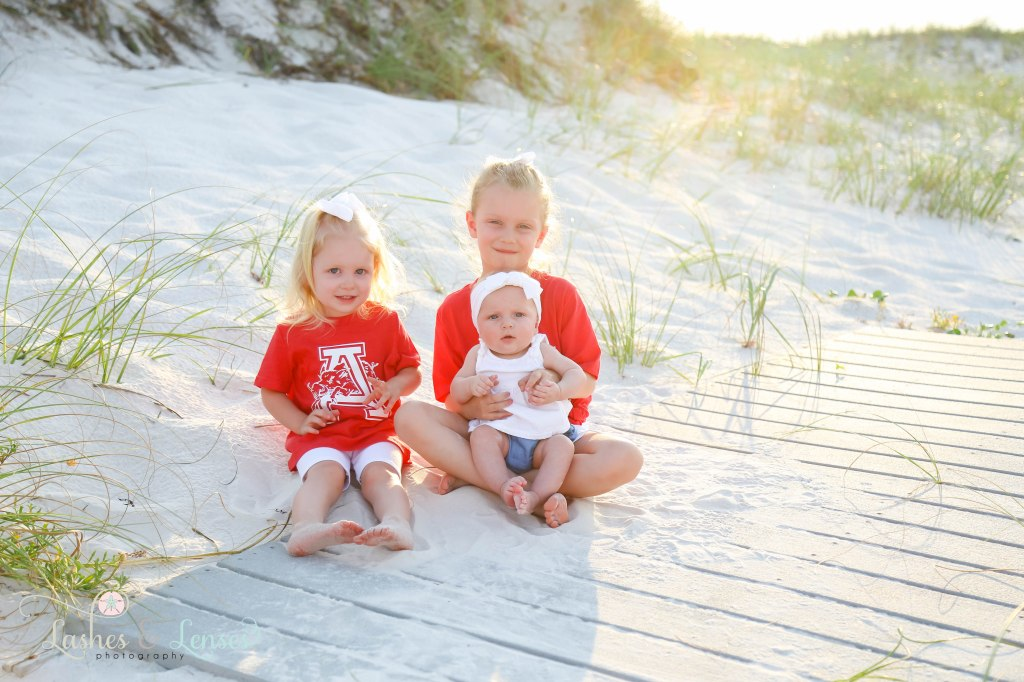 Three sisters under the age of six sitting on a washed up boardwalk with the sun shining behind them at Johnsons Beach in Perdido Key Florida