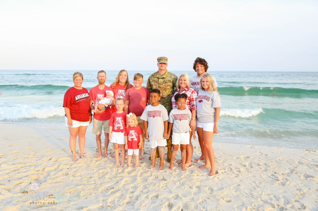 Large extended family with their son and uncle wearing his US Army uniform at Johnsons Beach in Perdido Key Florida