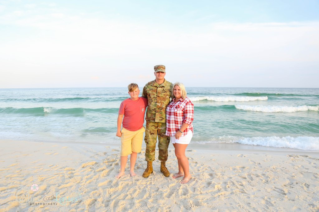 Mom with her son getting ready to go to basic training for the US Army and her younger son standing by the waters edge at Johnsons Beach in Perdido Key Florida