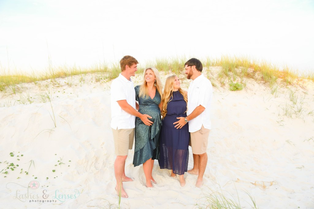 Two pregnant friends with their husbands holding their wives belly's with the sand dunes behind them at Johnsons Beach in Perdido Key Florida
