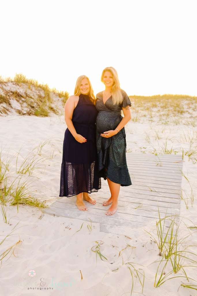 Two pregnant friends standing on the boardwalk with the sunset behind them at Johnsons Beach in Perdido Key Florida