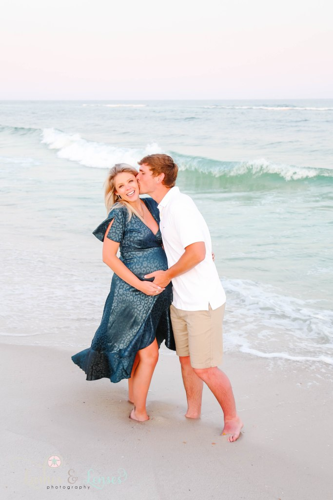Husband kissing wife's cheek pregnant wife next to the water at Johnsons Beach in Perdido Key Florida