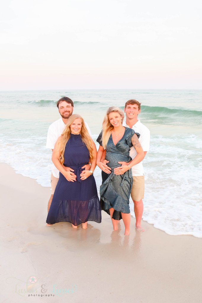 Two pregnant friends with their husbands holding their wives belly's with the water next to them at Johnsons Beach in Perdido Key Florida