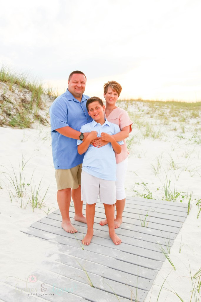 Mom and Dad with pre-teen son standing on a washed up boardwalk with the sunset behind them at Johnsons Beach in Perdido Key Florida