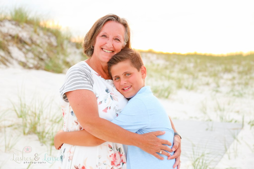 Grandma and grandson hugging with the sunset behind them at Johnsons Beach in Perdido Key Florida