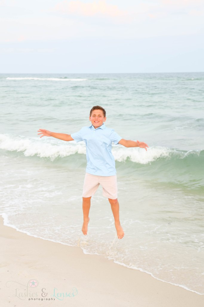 Pre-teen boy jumping in the water at Johnsons Beach in Perdido Key Florida