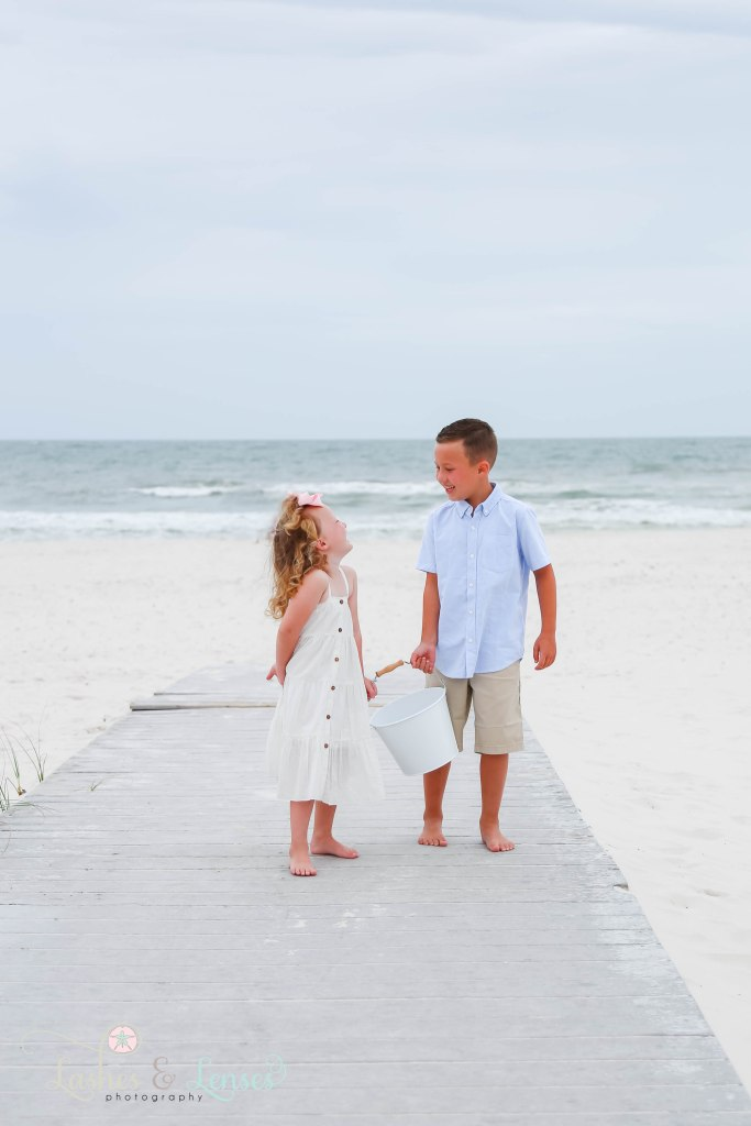 Brother and sister looking at each other and walking down the boardwalk with the water behind them at Johnsons Beach in Perdido Key Florida