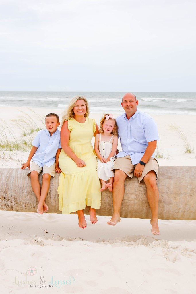 Mom and dad with their son and daughter sitting on a washed up palm tree at Johnsons Beach in Perdido Key Florida