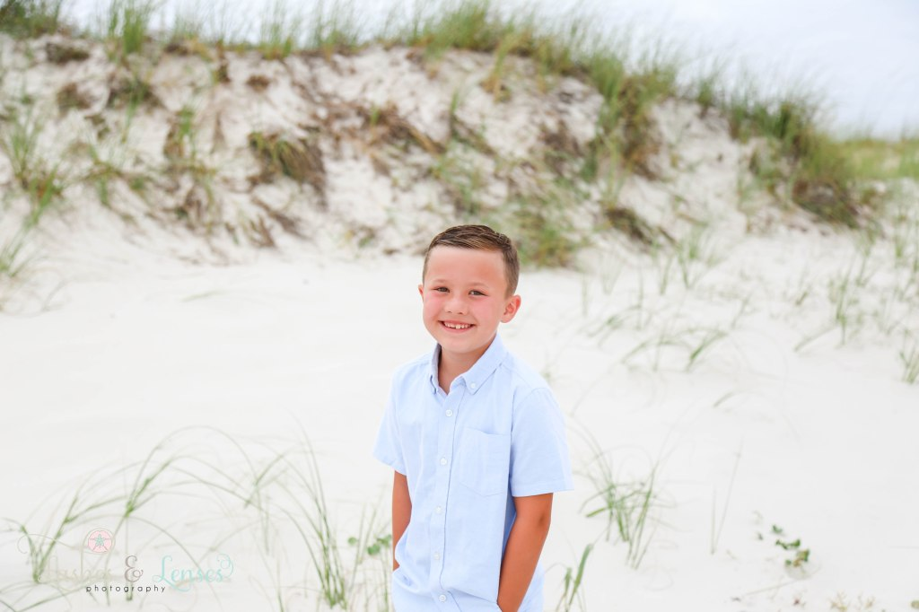 Young boy smiling and looking right at the camera with the sand dunes behind him at Johnsons Beach in Perdido Key Florida