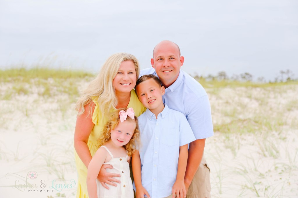 Parents with their son and daughter holding each other close next to the sand dunes at Johnsons Beach in Perdido Key Florida