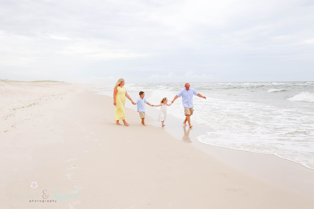 Family of four walking down by the water at Johnsons Beach in Perdido Key Florida