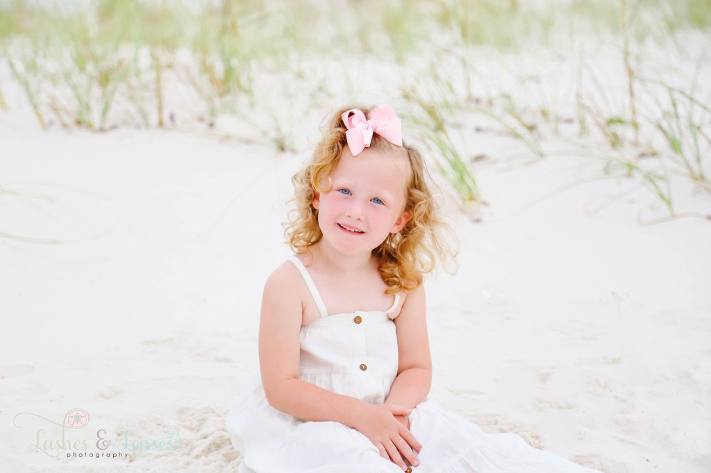 Little girl sitting in the sand at Johnsons Beach in Perdido Key Florida