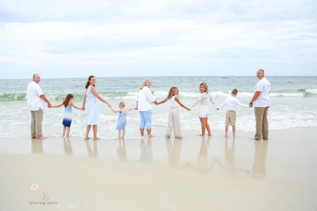 Extended family turning around and looking at the camera with the water in front of them at Johnsons Beach in Perdido Key Florida