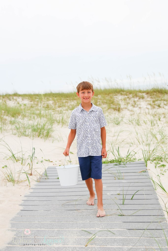 Elementary age boy walking down a washed up boardwalk and carrying a bucket at Johnsons Beach in Perdido Key Florida