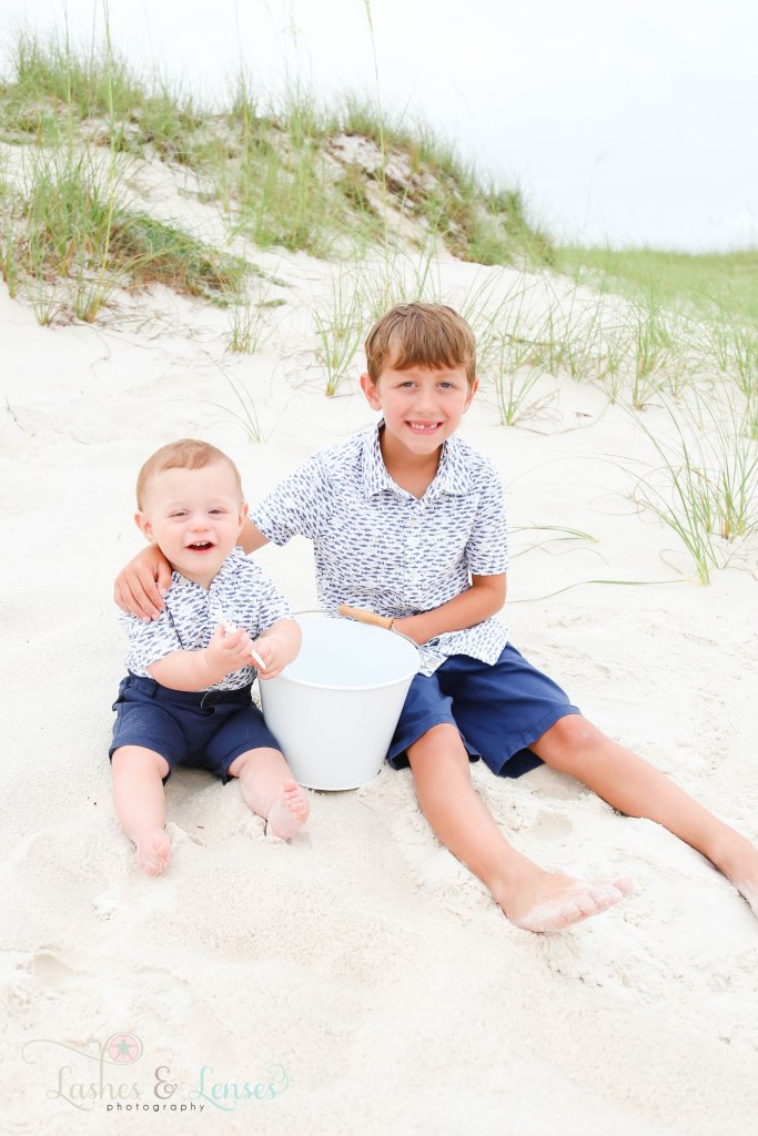 Brothers sitting in the sand and playing with a bucket at Johnsons Beach in Perdido Key Florida