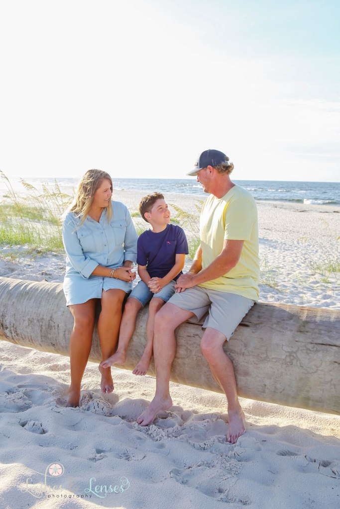 Mom, Dad and elementary age son sitting on a washed up palm tree with the water behind them at Johnsons Beach in Perdido Key Florida