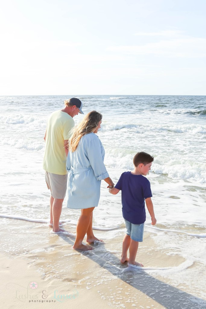 Mom, Dad and elementary age son looking at the water as the waves hit their feet at Johnsons Beach in Perdido Key Florida