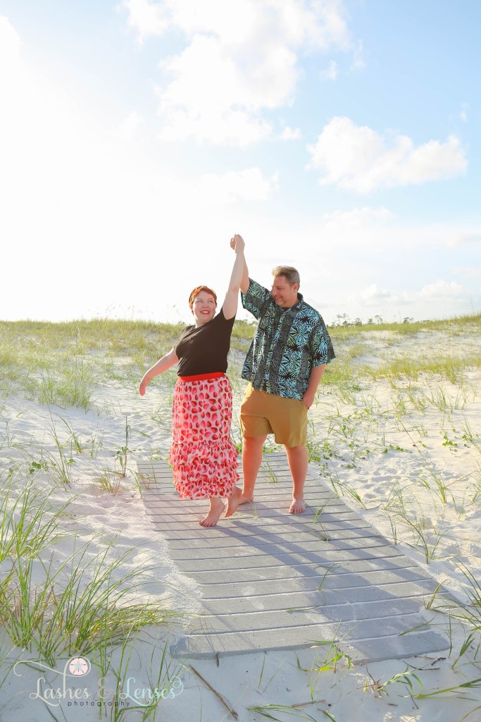 Husband twirling his wife on a washed up boardwalk at Johnsons Beach in Perdido Key Florida