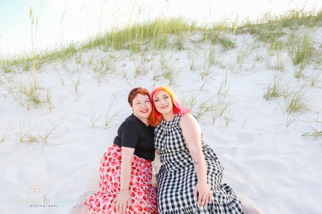 Sisters with beautiful vibrant hair sitting in the sand with the sand dunes behind them at Johnsons Beach in Perdido Key Florida