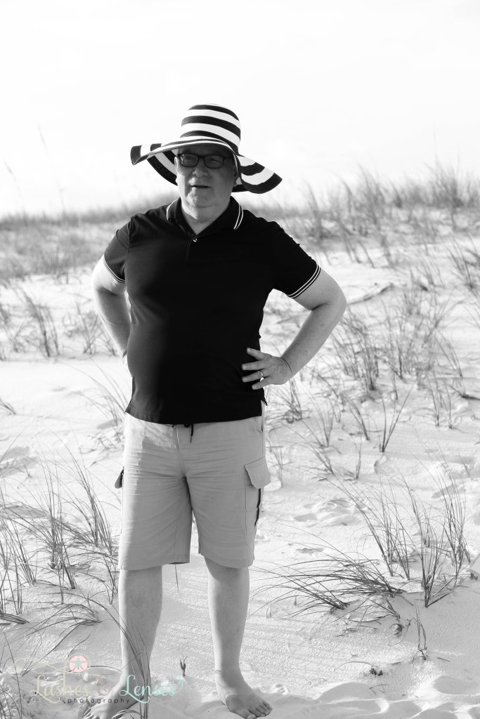 Black and White photo of granddad wearing his daughters striped sunhat at Johnsons Beach in Perdido Key Florida