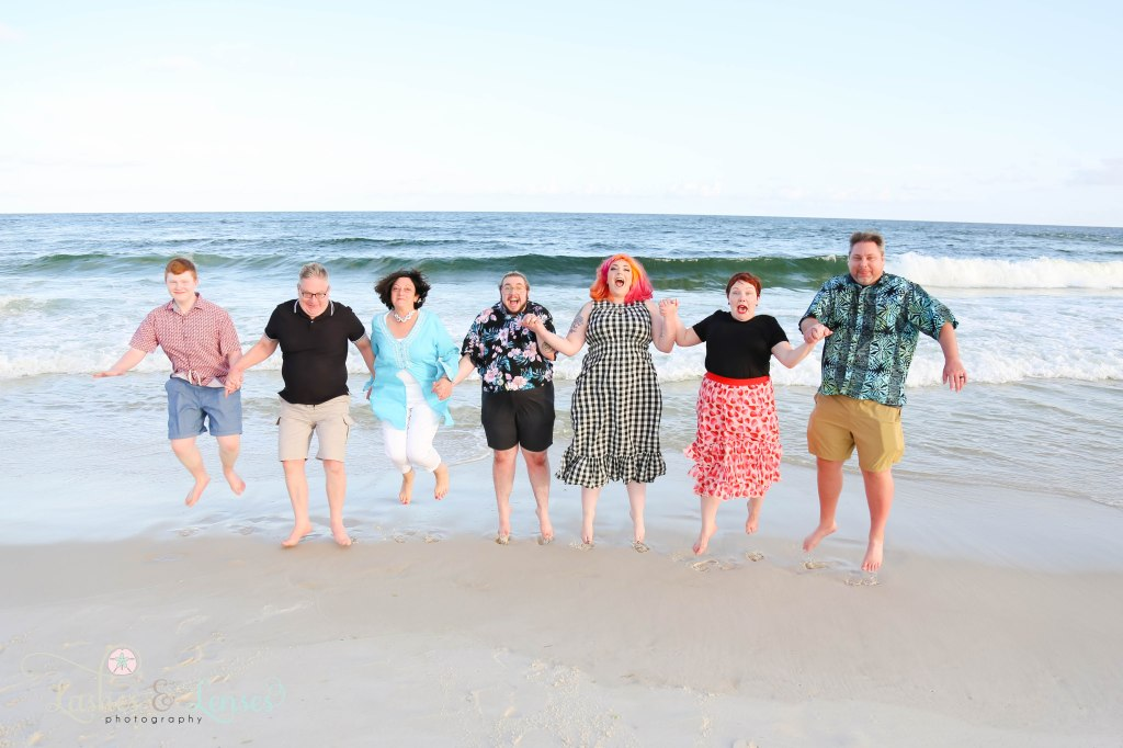 Large family all jumping in the air at the waters edge at Johnsons Beach in Perdido Key Florida
