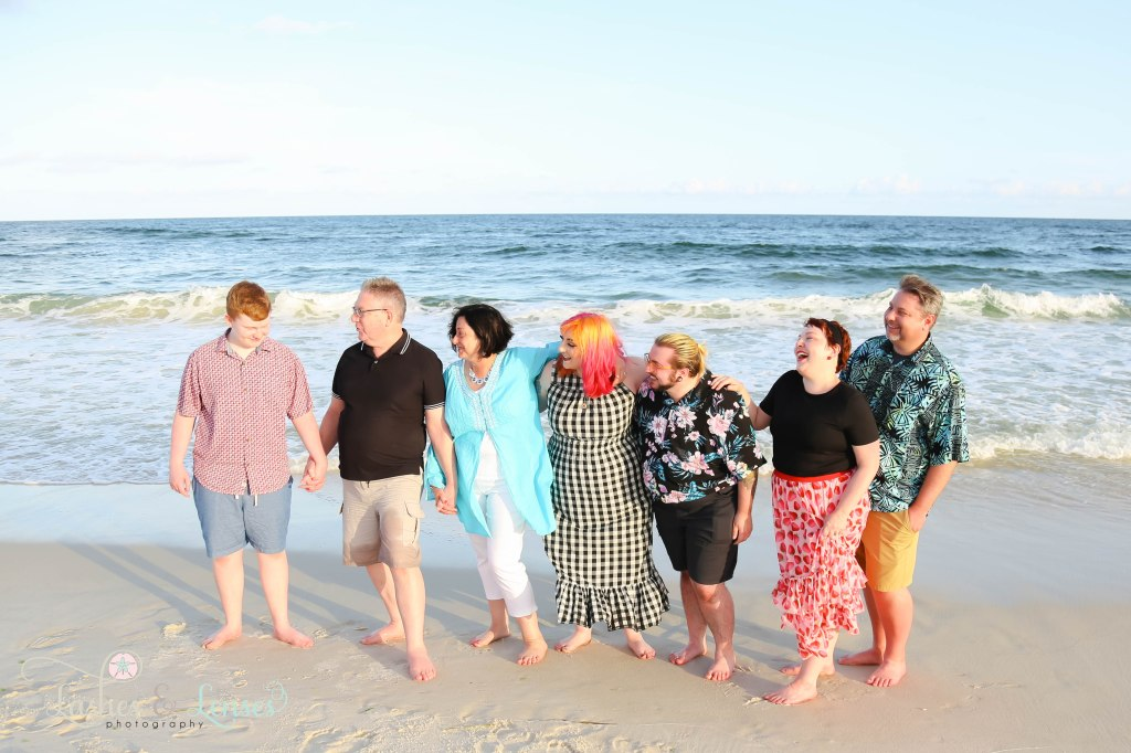 Extended family all looking at son and nephew and laughing at Johnsons Beach in Perdido Key Florida
