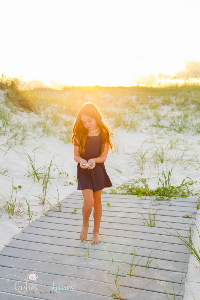Young girl holding a starfish with the golden sunlight on her hair and standing on a washed up palm tree at Johnsons Beach in Perdido Key Florida