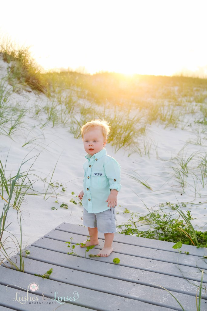 Toddler boy standing on a washed up boardwalk with the golden sunset behind him at Johnsons Beach in Perdido Key Florida
