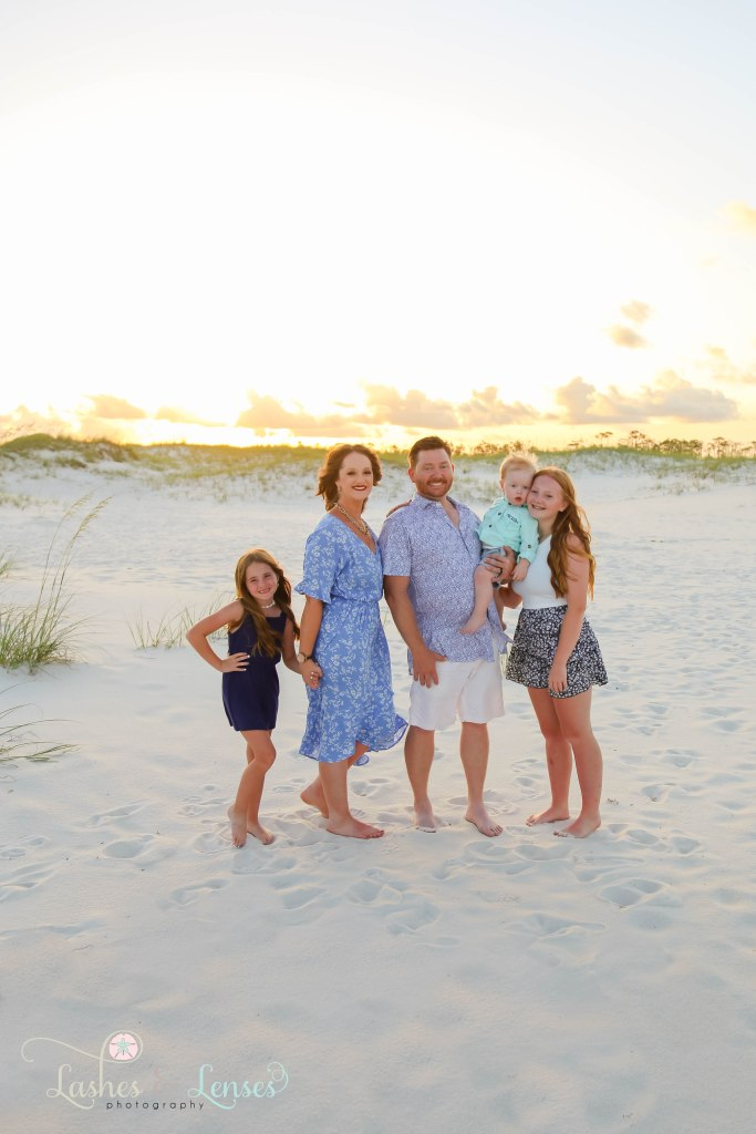 Mom, Dad and their two daughters and son standing on the sand with the sand dunes far behind them with the sunset behind them at Johnsons Beach in Perdido Key Florida