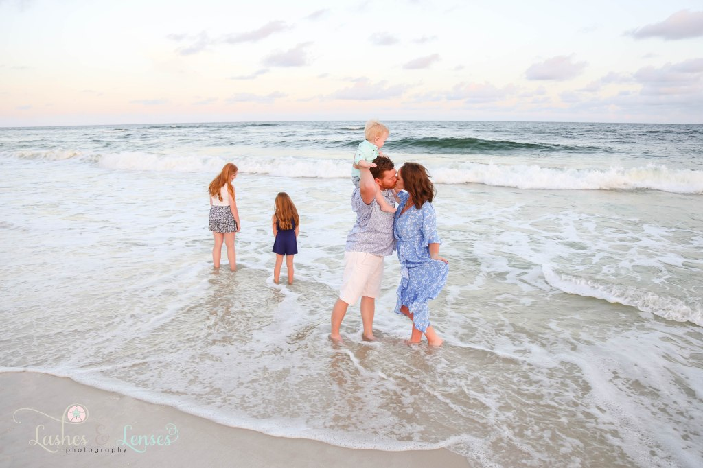 Husband and Wife Kissing while standing in the waves with their son sitting on his dads shoulders and their daughters standing in the water at Johnsons Beach in Perdido Key Florida