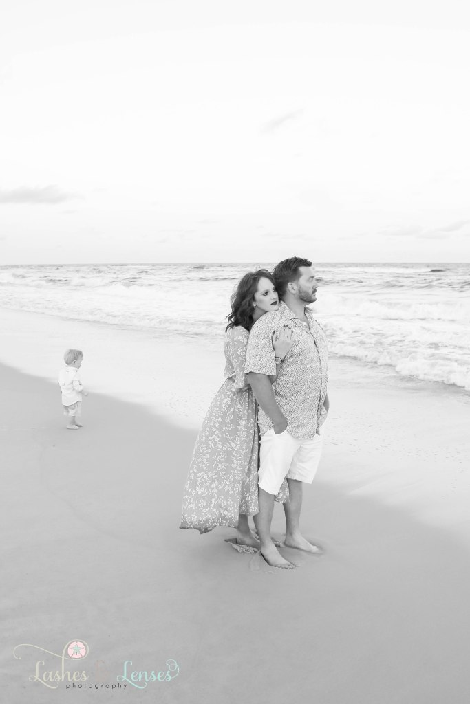 Black and White photo of wife hugging husbands from behind and their toddler son standing behind them next to the water at Johnsons Beach in Perdido Key Florida