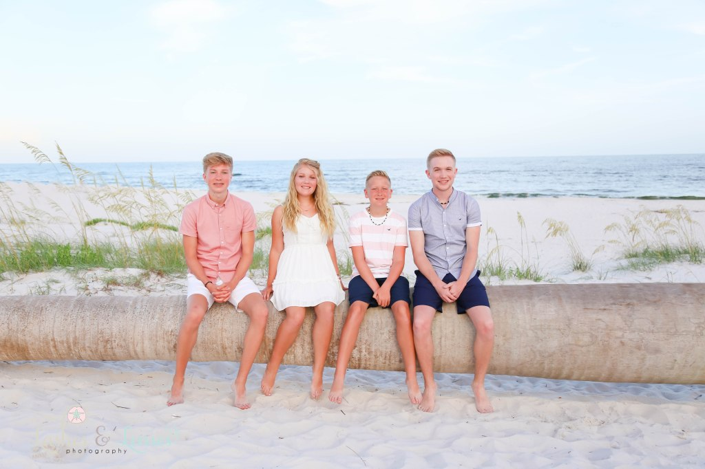 Three brothers and one sister sitting on a washed up palm tree with the gulf behind them at Johnsons Beach in Perdido Key Florida