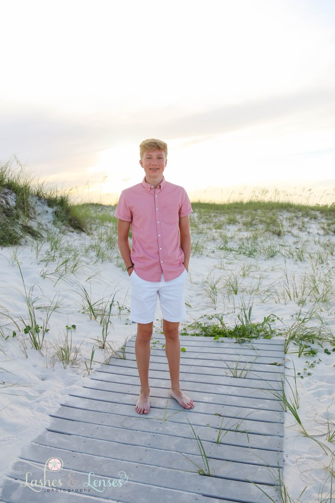 Senior boy standing on a washed up boardwalk with the sunset behind him at Johnsons Beach in Perdido Key Florida