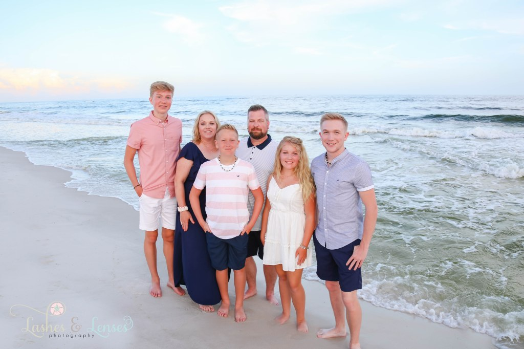 Family standing down next to the gulf at Johnsons Beach in Perdido Key Florida