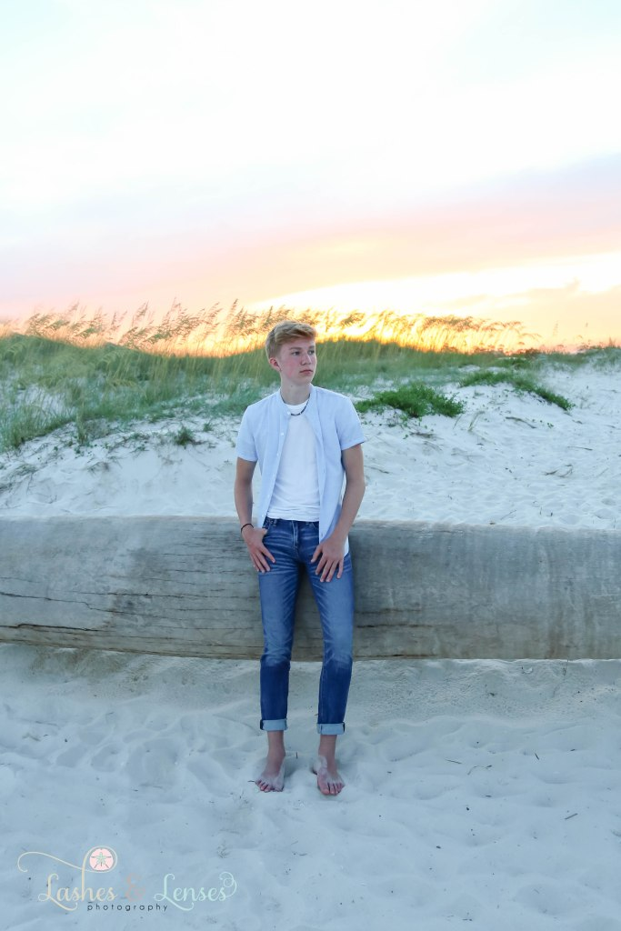 Senior boy leaning against a washed up palm tree with the colorful sunset behind them at Johnsons Beach in Perdido Key Florida