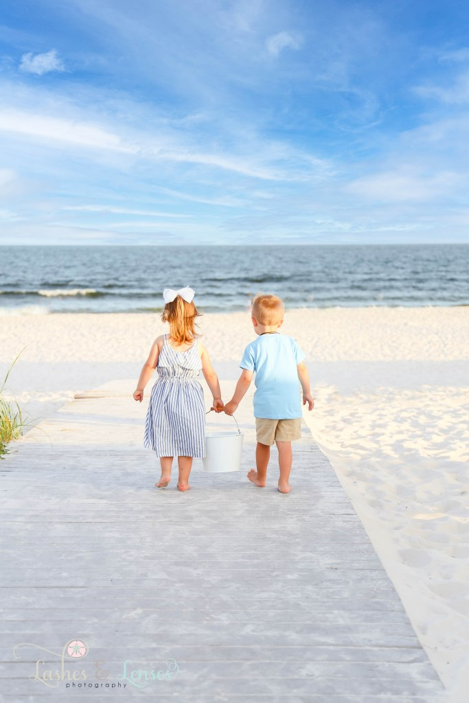Toddler boy/girl cousins holding a sand bucket between them and walking down the boardwalk towards the water at Johnsons Beach in Perdido Key Florida