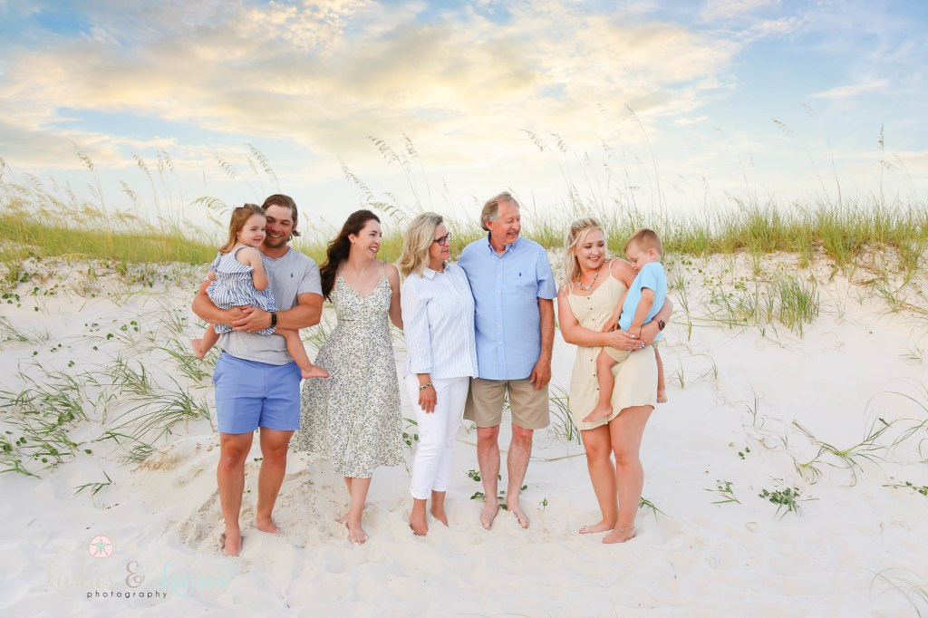 Extended family all look at mom and her toddler boy with sand dunes and sea oats behind them at Johnsons Beach in Perdido Key Florida