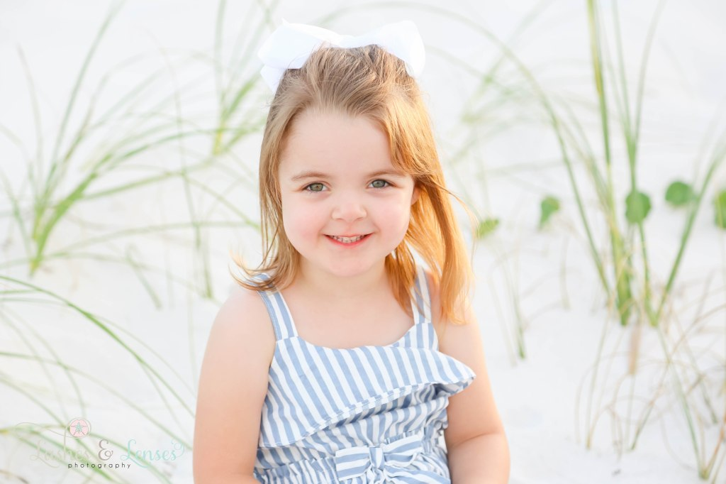 Close up photo of toddler girl with big white bow in her hair at Johnsons Beach in Perdido Key Florida